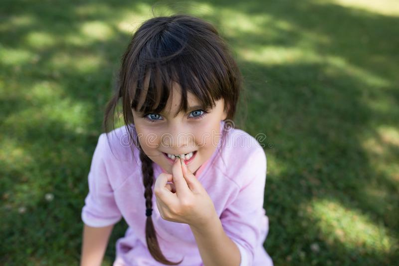 Meisje die met blauwe ogen op gras zitten stock foto's