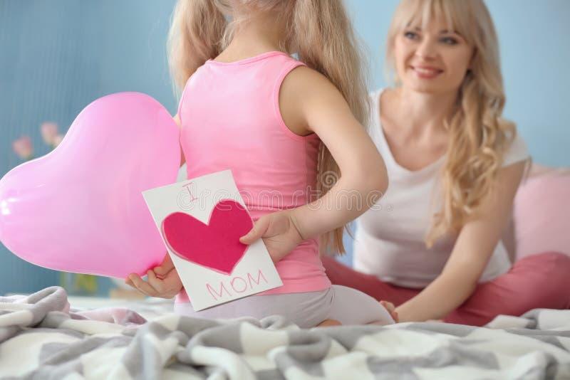 Meisje die met de hand gemaakte kaart en ballon voor moeder achter haar terug in slaapkamer verbergen stock foto's