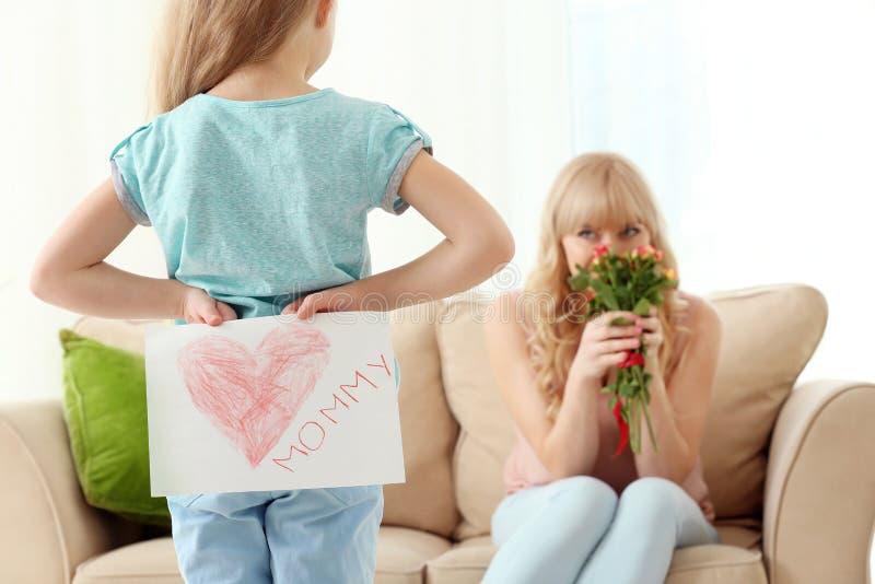 Meisje die met de hand gemaakte kaart voor moeder achter achter haar verbergen thuis, close-up stock afbeelding