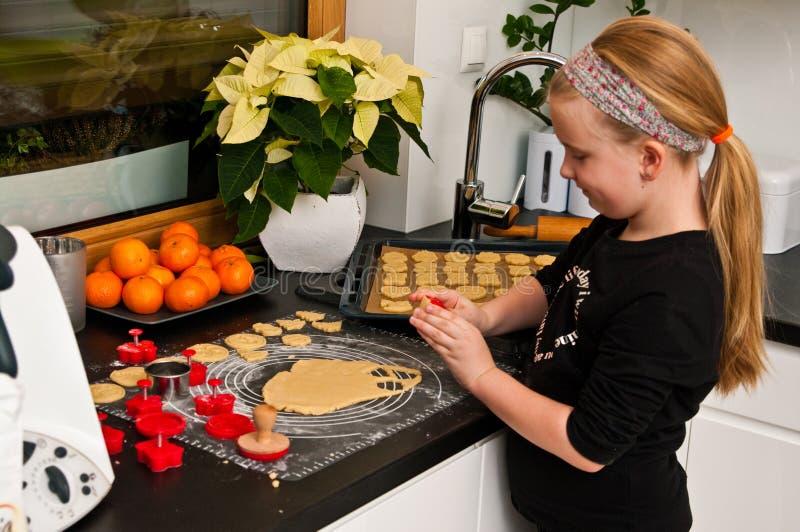 Meisje die met gemberkerstmis het koken helpen stock afbeeldingen
