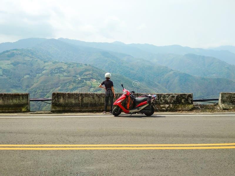 Meisje die met haar autoped van mooie mening van bergenlandschap genieten royalty-vrije stock foto