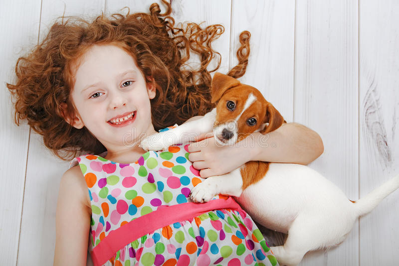 Meisje die met haar puppyvriend omhelzen stock foto