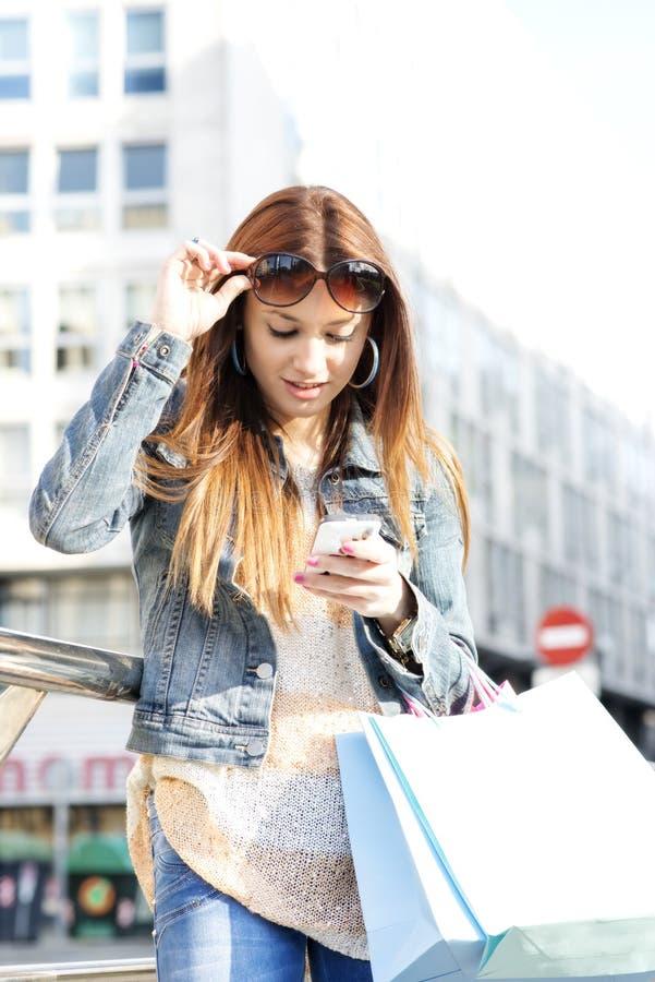 Meisje die met het winkelen zakken bericht op telefoon, openlucht kijken. royalty-vrije stock fotografie