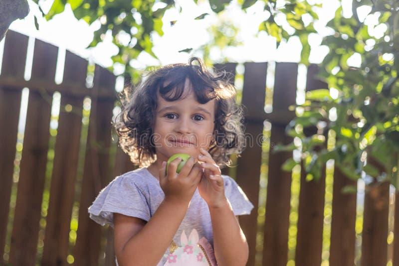 Meisje die met krullend haar een appel houden royalty-vrije stock afbeeldingen