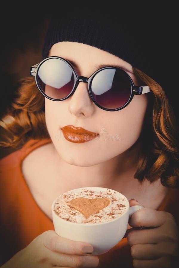 Meisje die met krullend haar een kop van koffie houden stock afbeeldingen