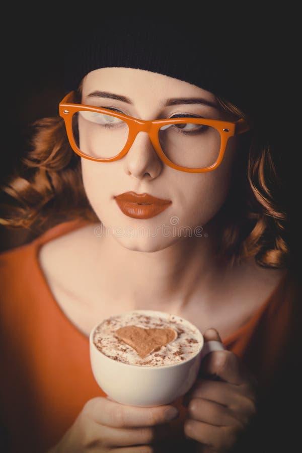 Meisje die met krullend haar een kop van koffie houden stock afbeelding