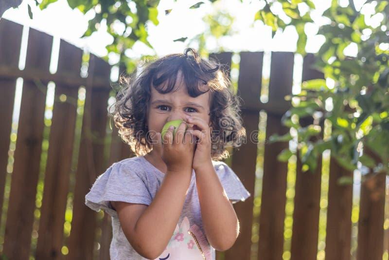 Meisje die met krullend haar van een appel eten royalty-vrije stock fotografie