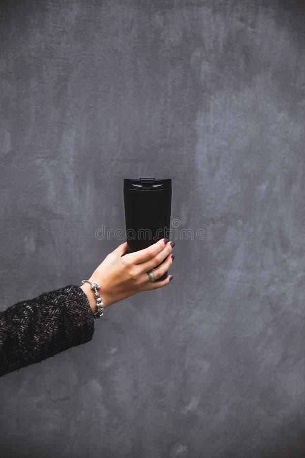 Meisje die met mooie manicurehand een zwarte vacuümtuimelschakelaar op een grijze achtergrond houden royalty-vrije stock foto