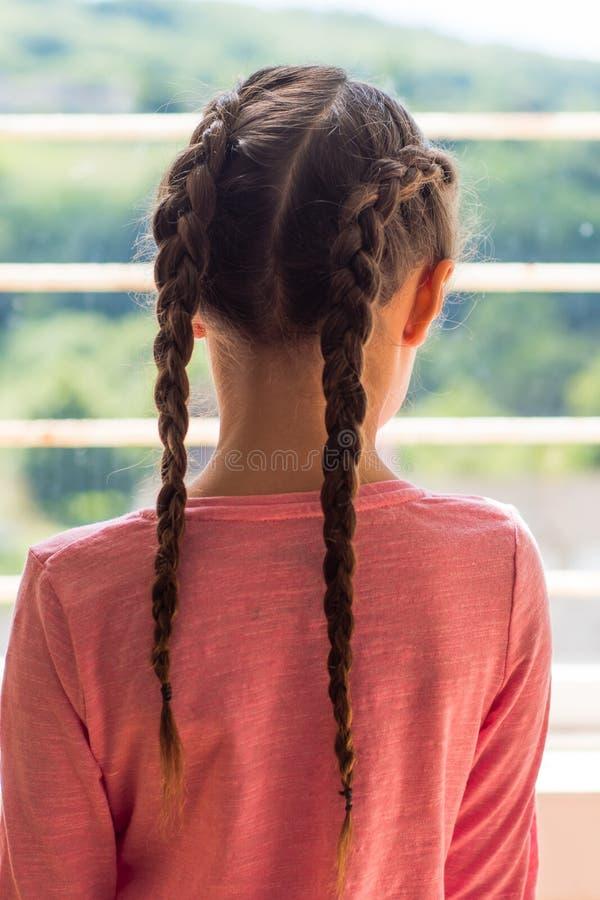 Meisje die met Nederlandse vlechten uit venster erachter kijken van stock afbeelding