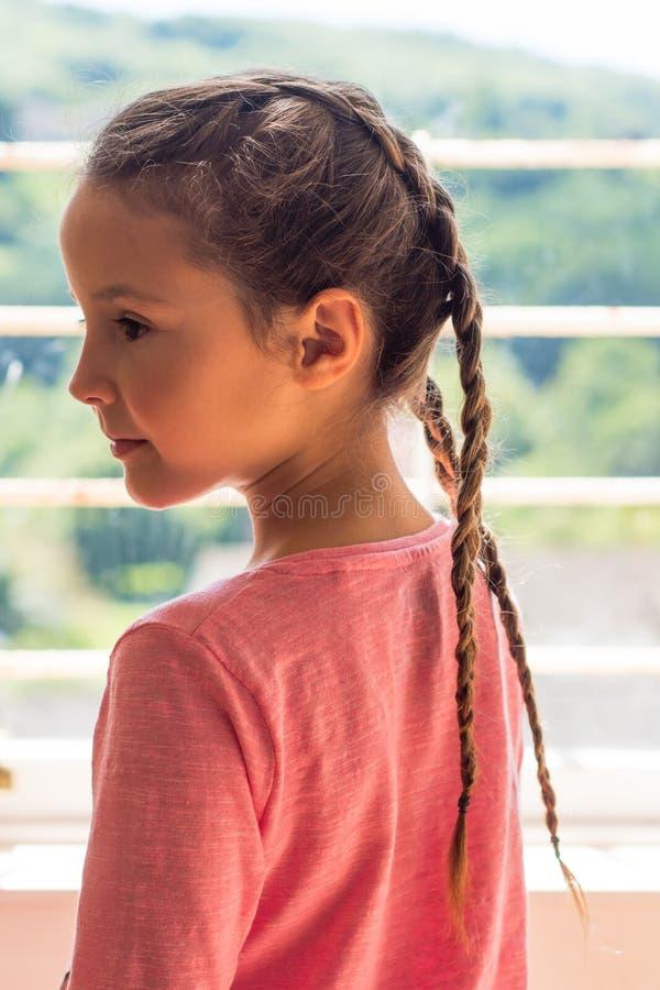 Meisje die met Nederlandse vlechten uit venster in profiel kijken stock foto's