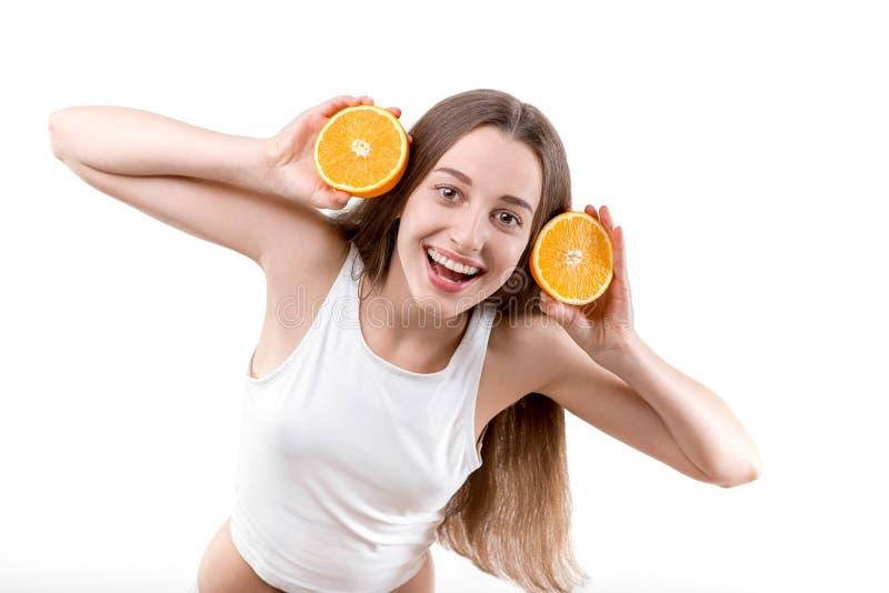 Meisje die met oranje hoofdtelefoons glimlachen stock foto's