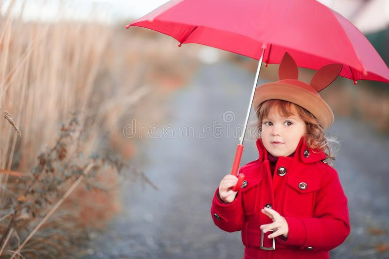 Meisje die met paraplu, de herfstdag lopen stock foto's