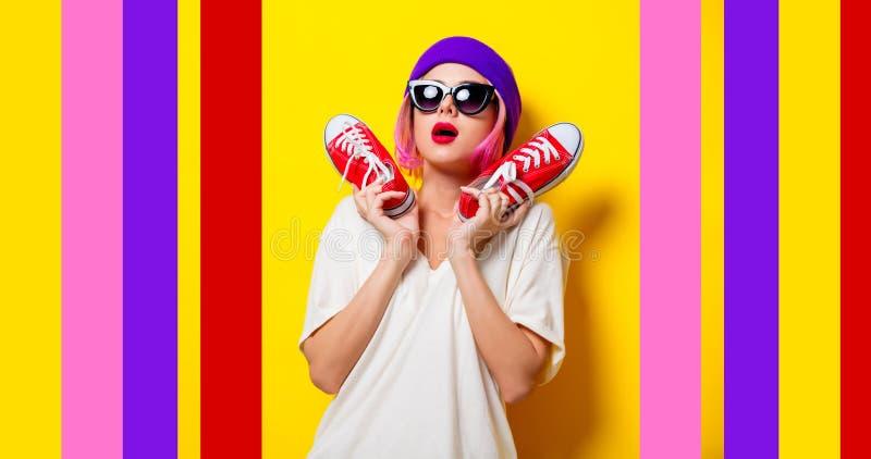 Meisje die met roze haar rode gumshoes houden royalty-vrije stock afbeeldingen