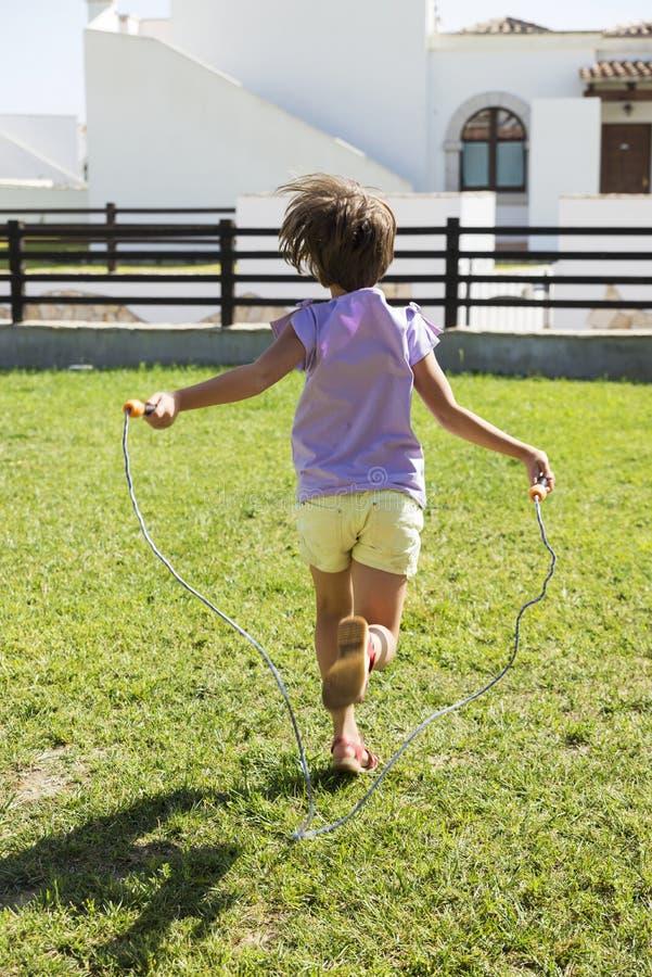 Meisje die met touwtjespringen springen stock foto