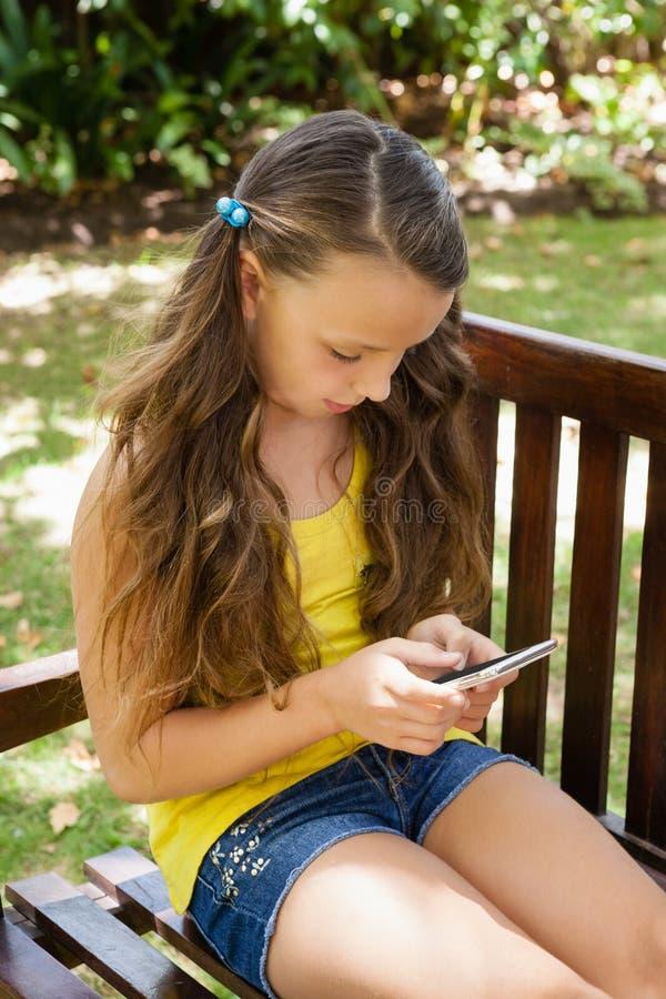 Meisje die mobiele telefoon met behulp van terwijl het zitten op houten bank stock afbeelding