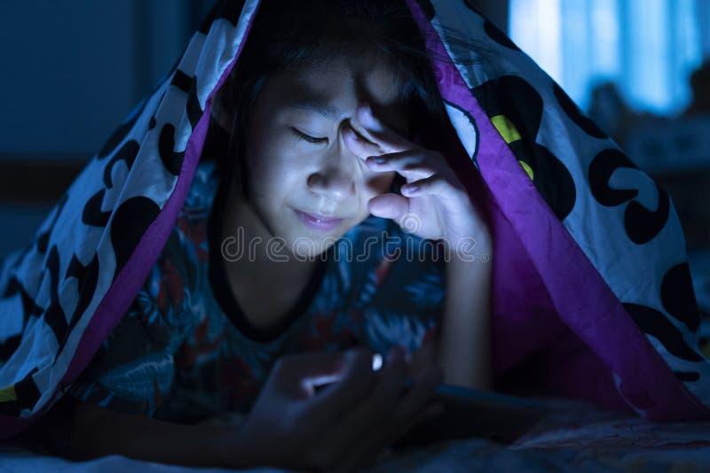 Meisje die mobiele telefoon op donker bed in de slaapkamer met behulp van royalty-vrije stock fotografie