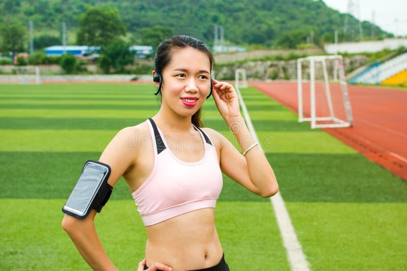 Meisje die modern technologiemateriaal voor jogging plaatsen royalty-vrije stock afbeelding