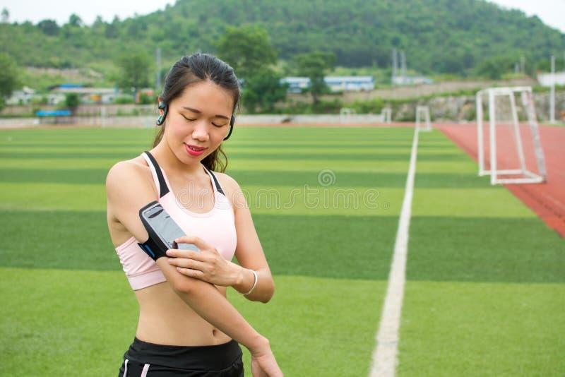 Meisje die modern technologiemateriaal voor jogging plaatsen stock foto