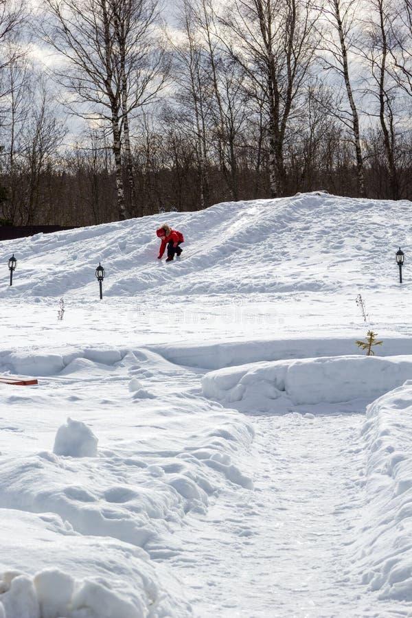 Meisje die neer van een sneeuwheuvel rollen stock afbeeldingen