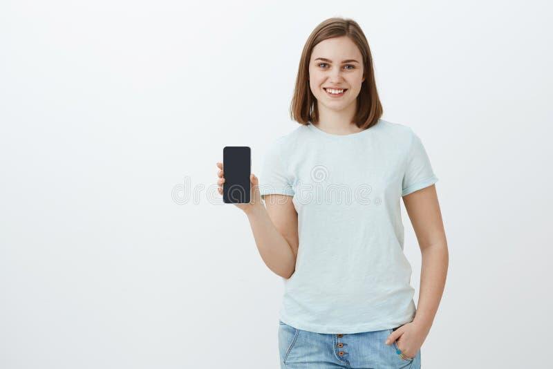 Meisje die nieuwe die telefoonouders tonen voor nieuwe schooltermijn worden gekocht Opgetogen en tevreden charmante jonge vrouw d royalty-vrije stock fotografie