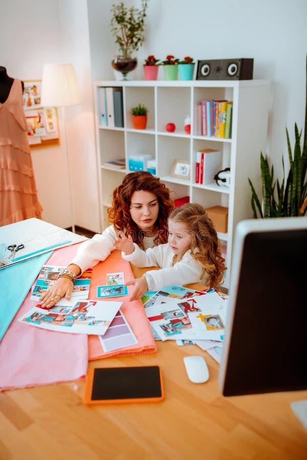 Meisje die nieuwsgierig bezoekend mamma voelen die als ontwerper op het werk werken stock foto's