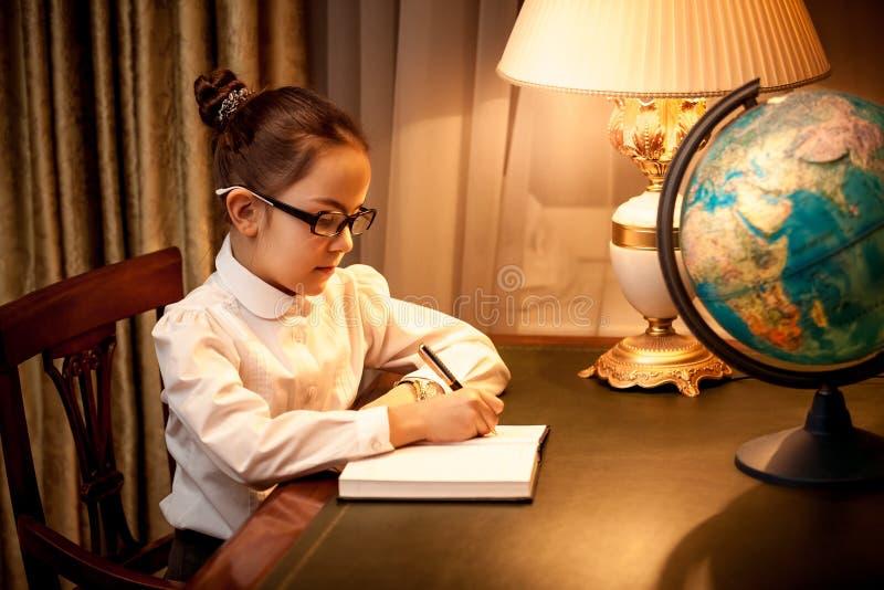 Download Meisje Die In Notitieboekje Bij Bureau Met Bol Schrijven Stock Foto - Afbeelding bestaande uit levensstijl, klassiek: 39100102