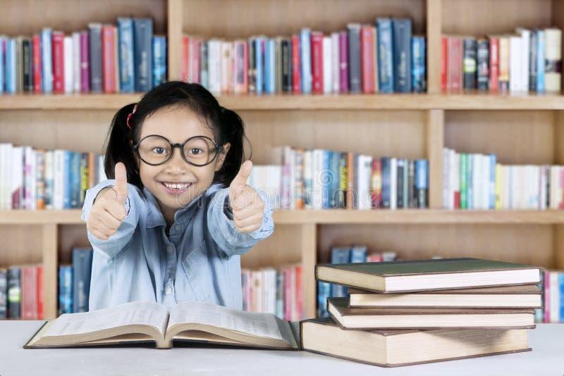 Meisje die o.k. gebaar in bibliotheek tonen royalty-vrije stock afbeelding