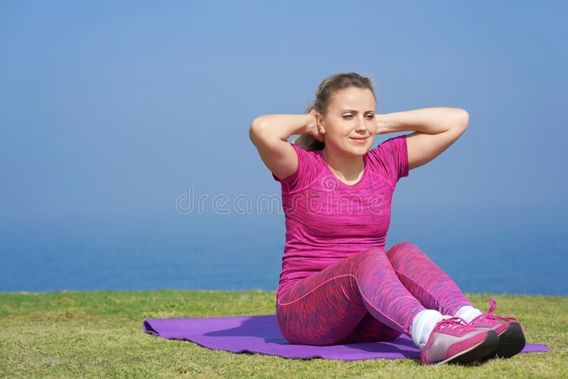 Meisje die oefeningen doen die op de achtergrond van het overzees zitten stock fotografie
