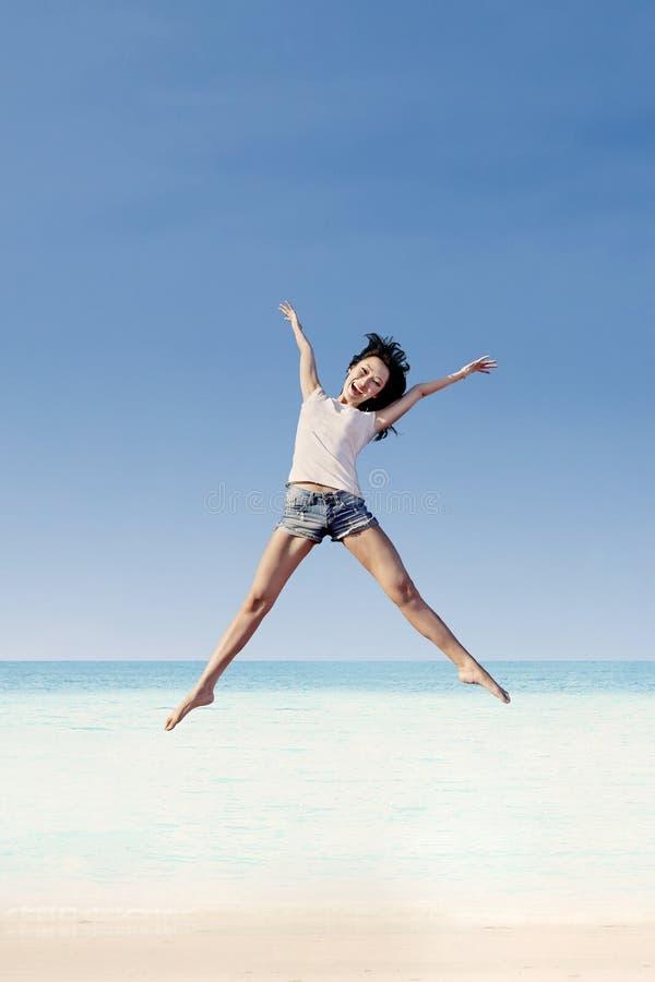 Meisje die onder blauwe hemel springen stock foto's
