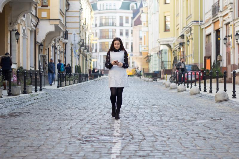 Meisje die onderaan de straat met haar telefoon lopen stock fotografie