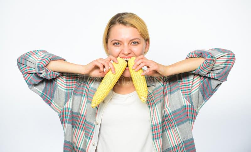 Meisje die ongekookt en onverwerkt voedsel eten De vrouwenlandbouwer eet twee gele maïskolven op witte achtergrond Sterke tanden stock afbeeldingen