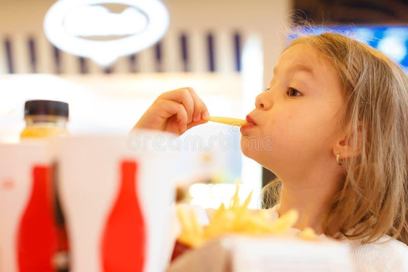 Meisje die ongezond voedsel eten stock afbeelding