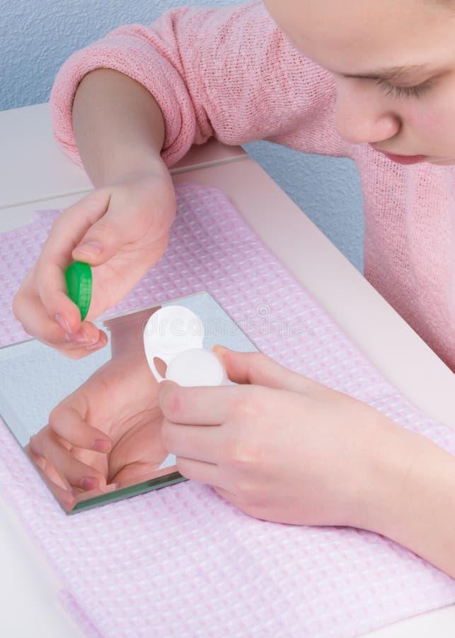 Meisje die oogkleur met contactlenzen op vakantie voorbereidingen treffen te veranderen stock fotografie