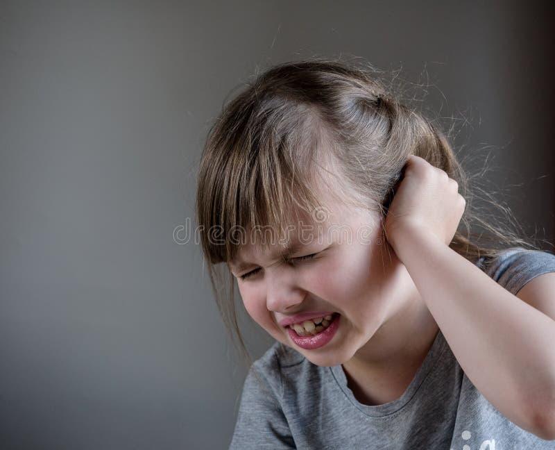 Meisje die oorpijn wat betreft zijn pijnlijk die hoofd hebben op grijze achtergrond wordt geïsoleerd stock foto's