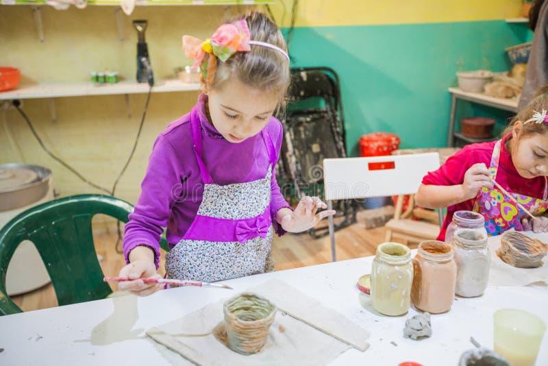 Meisje die op Aardewerkworkshop Clay Vase schilderen stock fotografie