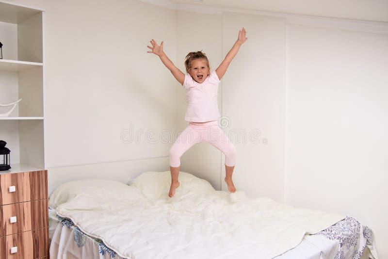 Meisje die op bed thuis springen stock afbeeldingen