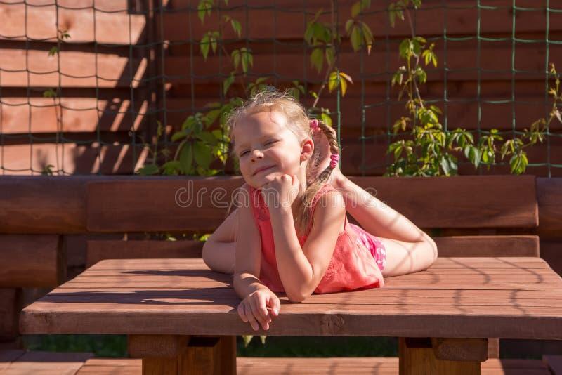 Meisje die op de lijst in houten as liggen royalty-vrije stock foto