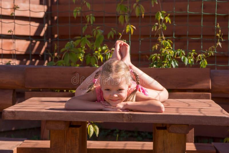 Meisje die op de lijst in houten as liggen royalty-vrije stock fotografie