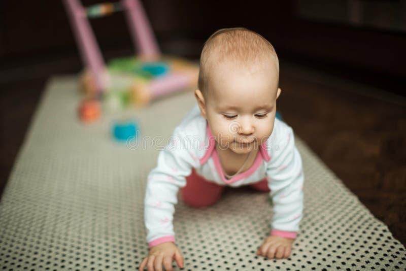 Meisje die op de vloer op het tapijt thuis kruipen stock foto's