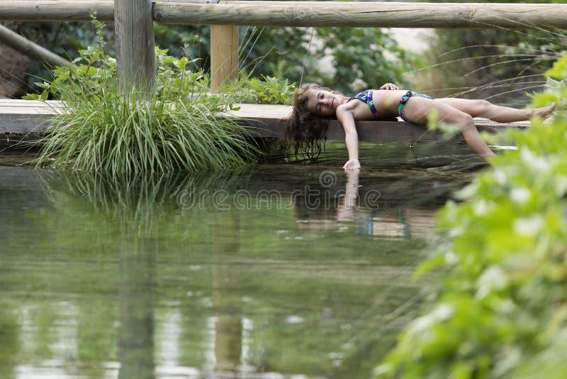 Meisje die op de voetgangersbrug van een meer liggen stock afbeelding