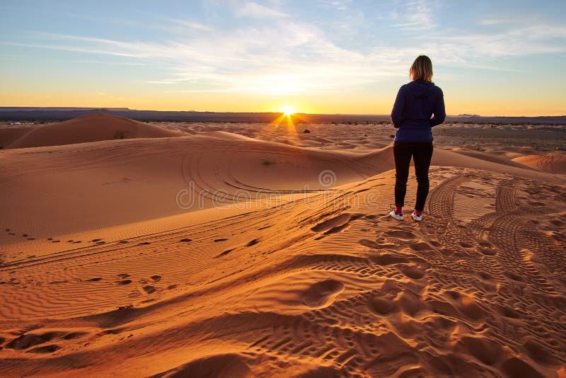 Meisje die op de zonsopgang op het zandduin letten in de woestijn van de Sahara stock afbeelding