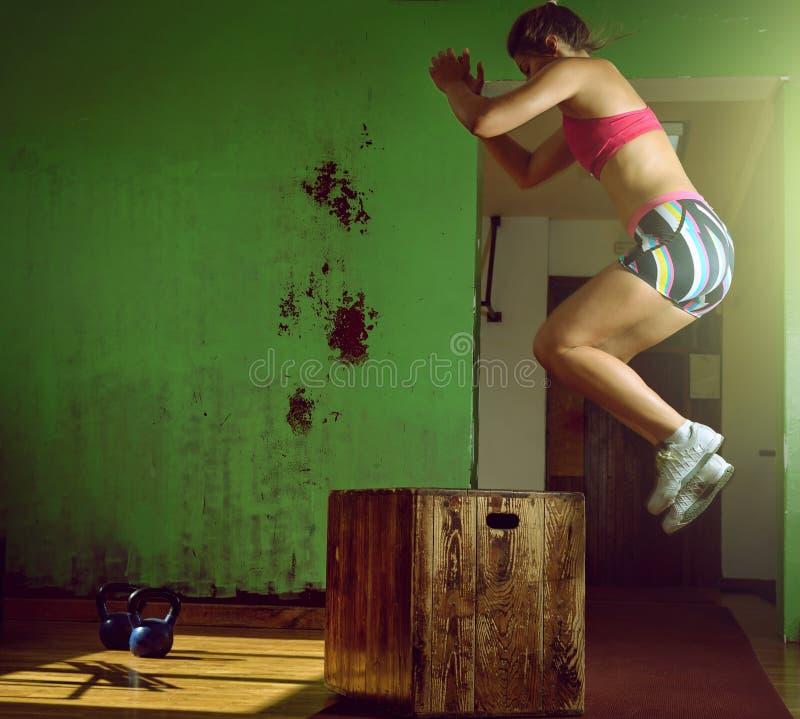 Meisje die op doos in gymnastiek springen stock foto