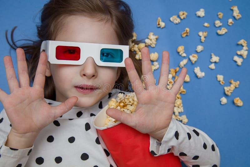Meisje die op een film in 3D glazen met popcorn letten stock foto's