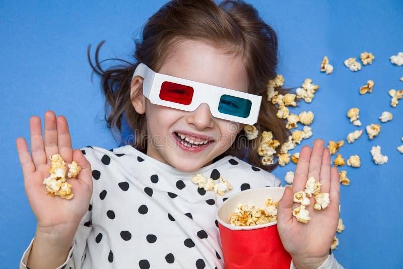 Meisje die op een film in 3D glazen met popcorn letten stock afbeelding