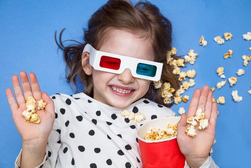 Meisje die op een film in 3D glazen met popcorn letten royalty-vrije stock foto's