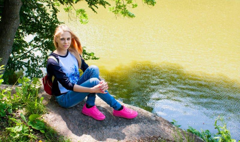 Meisje die op een grote rots rusten stock afbeelding