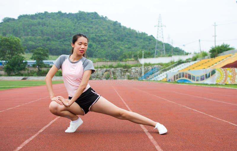 Meisje die op een joggingspoor opwarmen stock foto