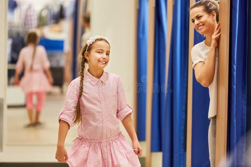 Meisje die op een kleding proberen terwijl het winkelen stock foto's