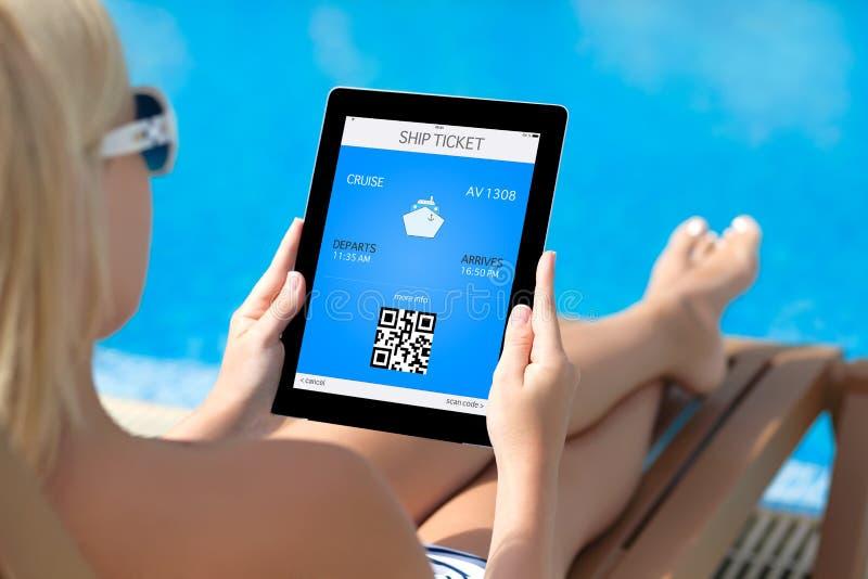 Meisje die op een ligstoel door de pool liggen en een tablet houden met stock foto