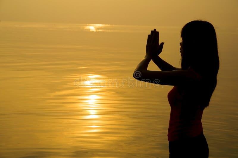 meisje die op een strand bidden royalty-vrije stock foto